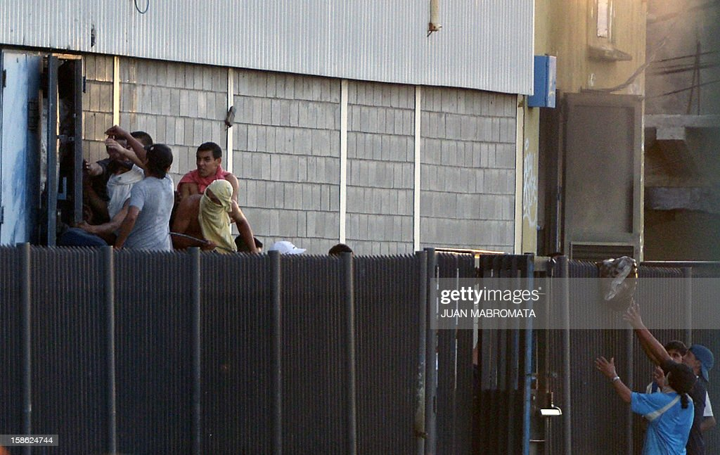 Men loot a supermarket through a lateral door in San Fernando, Buenos Aires province on December 21, 2012. Two people died Friday and two more were seriously injured as mobs looted supermarkets in Rosario, Argentina's third largest city, an official said. A series of lootings have taken place in five other cities of Argentina since Thursday leaving also near a hundred people injured and 300 detained.