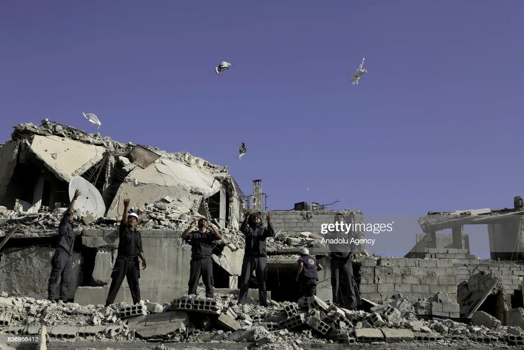 Men, members of Syrian civil defense organization, White Helmets let a white pigeon to fly for people who lost his life in chemical attack that in the Eastern Ghouta region of Damascus, Syria on August 22, 2017. It is the 4th anniversary of chemical weapons attack near countrysides of Zamalka that Assad Regime's forces carried out.