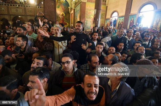 Men mourn for the victims of the blast at the Coptic Christian Saint Mark's church in Alexandria the previous day during a funeral procession at the...