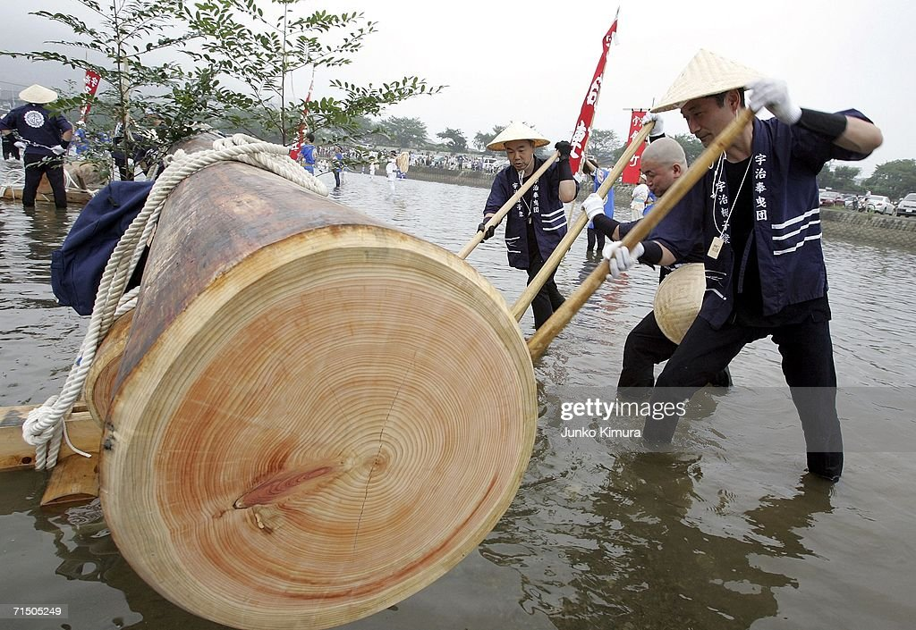 Men move wood into place to be pulled along the Isuzu River to the Inner Shrine of Japan's biggest shrine ?Ise Jingu? during the 62nd Okihiki-Gyoji ceremony on July 23, 2006 in Ise, Mie Prefecture, Japan. The Okihiki-Gyoji ceremony is conducted every 20 years for the last 1300 years and involves the shrines of Ise Jingu being moved and reconstructed and is called the Sengu, it is believed that by performing the Sengu the Japanese people will have their blessings renewed.