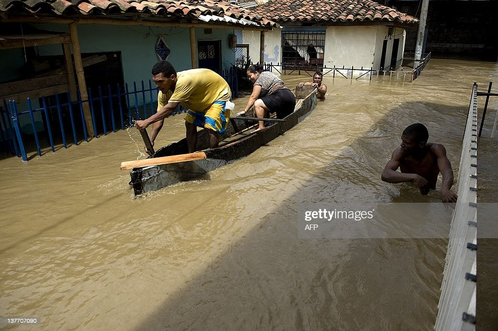 Men navigate a pirogue along a flooded street, following the overflowing of the Cauca river, on January 25, 2012 in Candelaria, department of Valle del Cauca, Colombia. According to an official report, about 3 million people have been affected by heavy rains caused by the phenomenon of 'La Nina' since the second half of 2010. AFP PHOTO / Luis ROBAYO