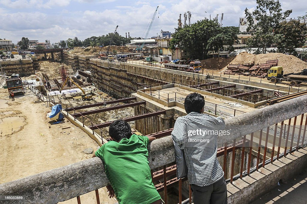 Men observe a construction site for the Bangalore Metro in Bangalore, India, on Saturday, Oct. 12, 2013. Reserve Bank of India Governor Raghuram Rajan has turned the rupee from a pariah to the worlds favorite currency after just a month in office as he intensifies efforts to quell inflation and lure capital. Photographer: Dhiraj Singh/Bloomberg via Getty Images