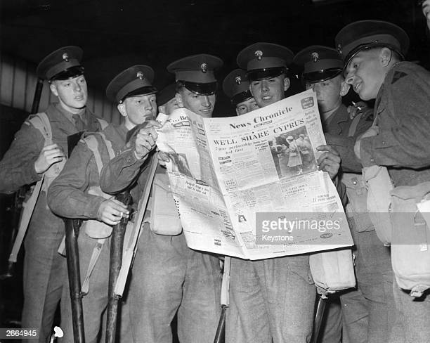 Men of the 2nd Battalion Grenadier Guards reading a newspaper at Abingdon in Oxfordshire They are waiting to board an aircraft bound for Cyprus