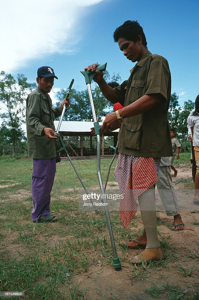 """Men of Veal Thom examine and adjust new crutches they received from Veterans International Cambodia on a trip to their village. Deep in the hinterlands, down a rutted dirt road, a small village shelters the remnants of Cambodia's civil war. Some 200 disabled veterans - both Khmer Rouge and government soldiers - and their families have moved to Veal Thom, or """"Big Field."""" There they build huts, grow rice, cultivate flowers and do what society will not allow in their homelands: live in peace. Though they lost limbs and parts of their lives in Cambodia's civil war, their wounds mark them as outcasts in the Cambodian society.."""