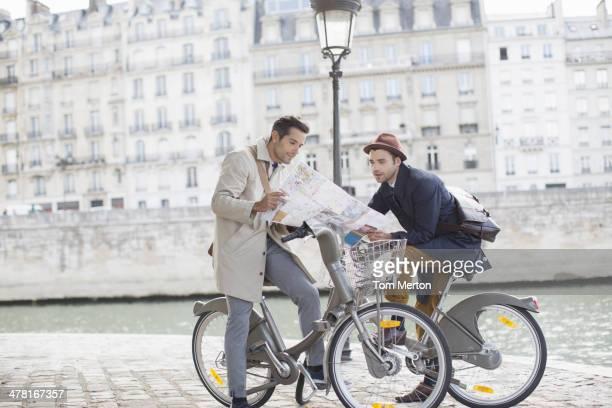 Mapa de lectura hombre en una bicicleta junto al río Seine, París, Francia