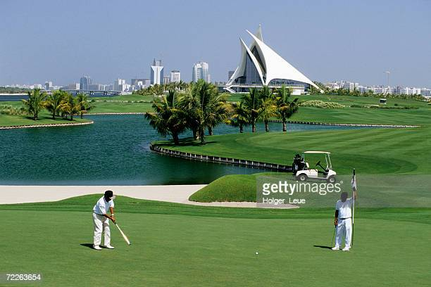 Men on Dubai Creek Golf with Yacht Club in distance, Dubai, United Arab Emirates