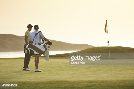 Men on golf course overlooking ocean
