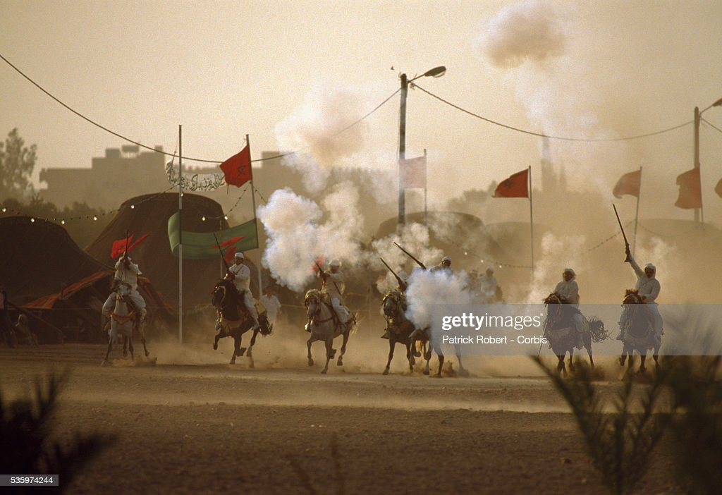 Men on horseback fire rifles in celebration of the wedding of Princess Lalla Asmaa, daughter of Hassan II, King of Morocco.
