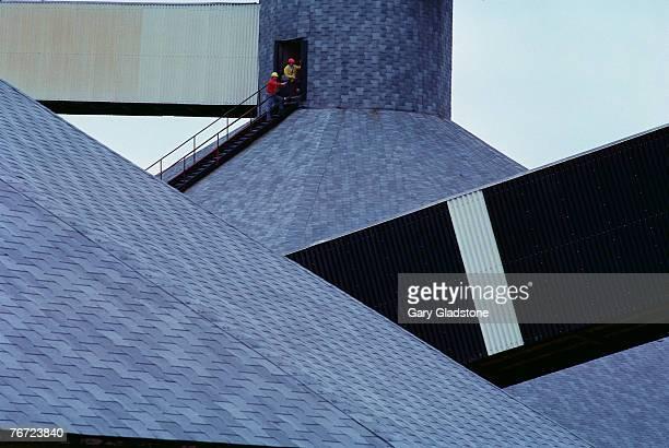 Men on industrial rooftops