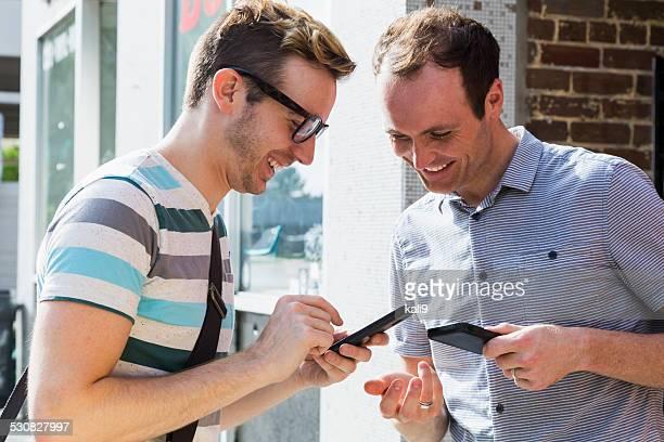 Men on street corner texting on mobile phones