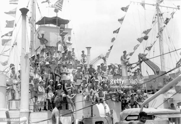 Men on the Tank Landing Ship HMS LST 538 cheer and celebrate as signal flags are hoisted upon word from Delhi announcing the end of hostilities in...