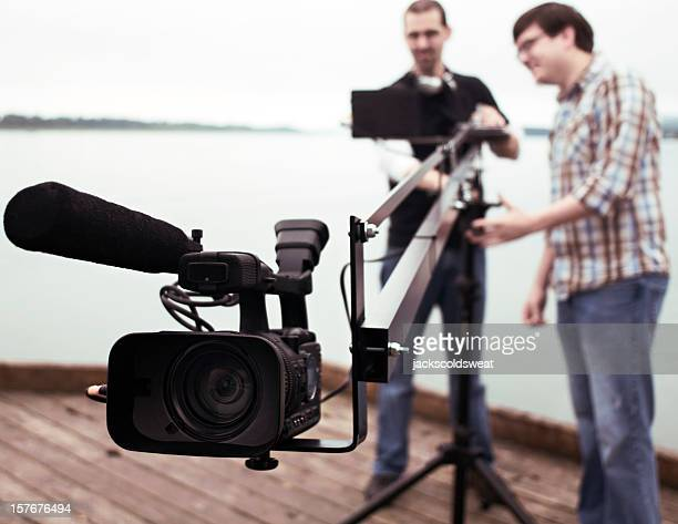 Men operating video camera on elongated tripod