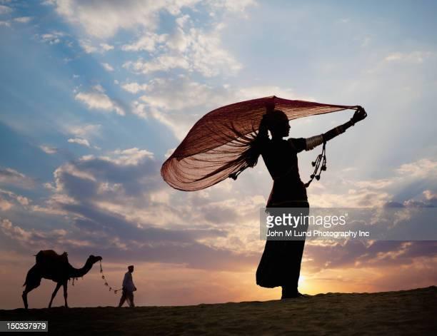 Homme à l'extérieur avec chameau au coucher du soleil