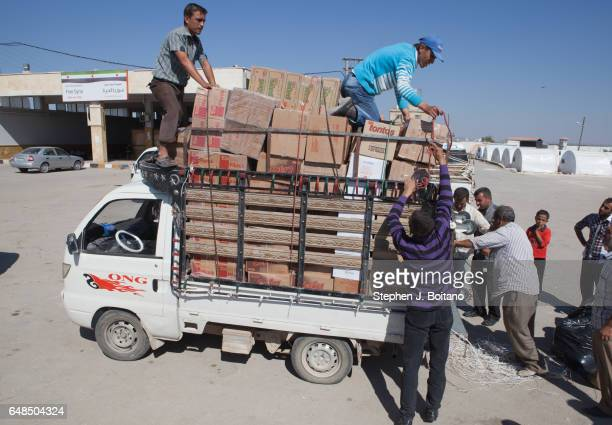 A'ZAZ ALEPPO SYRIA Men over load a truck with gods near the Syrian refugee camp at the border with Turkey in A'zaz Syria