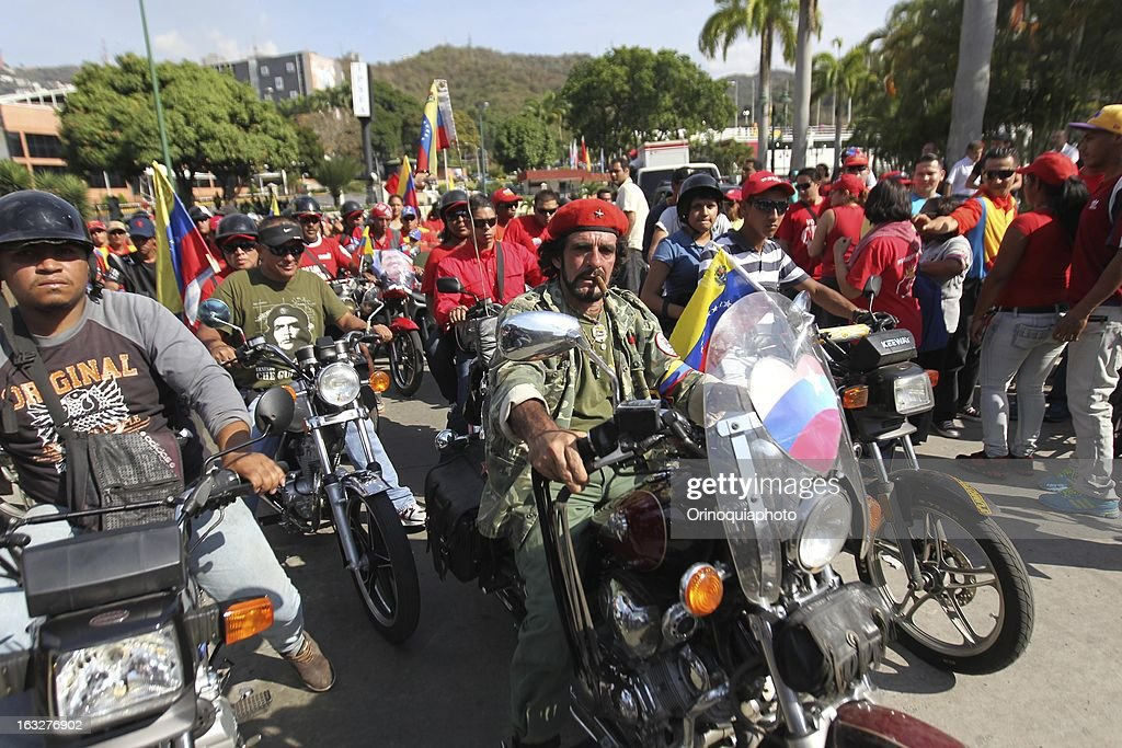 Men over wheels during the march of the supporters of President Hugo Chavez through the streets of Caracas to the military academy on March 06, 2013 in Caracas, Venezuela.