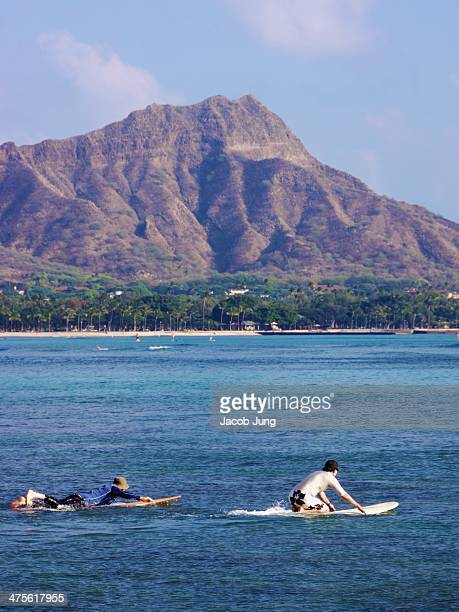 Men paddling out to surf off Waikiki beach with Diamond Head in the background