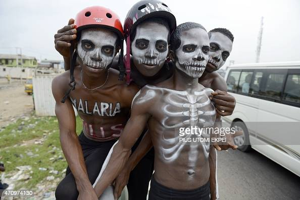Men painted like skeleton pose on April 24 2015 in Lagos to warn on the deadly disease prior to the World Malaria Day on April 25 Malaria kills every...