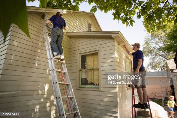 Men painting edge of house