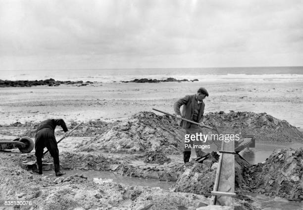 Men panning for tin on the beach at Porthtowan in Cornwall