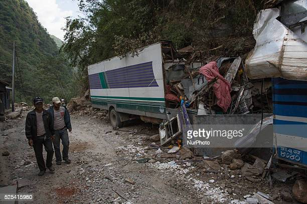 Men pass on the Kobani road as they look a damaged truck caused by the deadly earthquake near the Tibetan border Isolated Nepalese Villagers still...