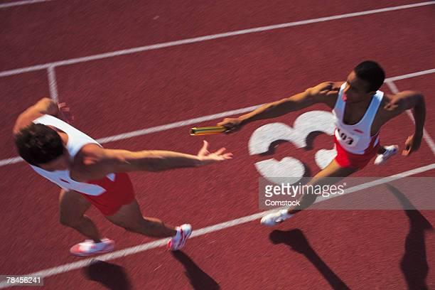 Men passing baton in relay race