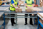 Men passing cardboard boxes along conveyor belt
