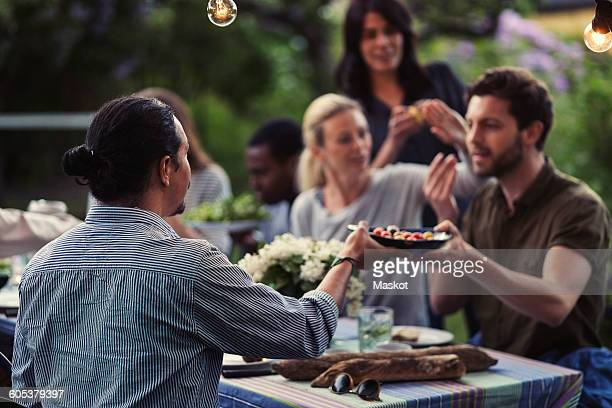 Men passing food at dining table during dinner party at yard