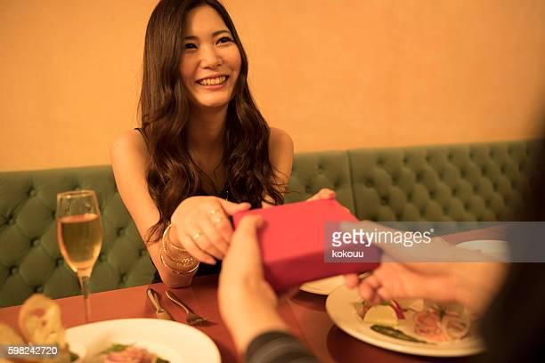 Men passing the gift to women in stylish restaurant