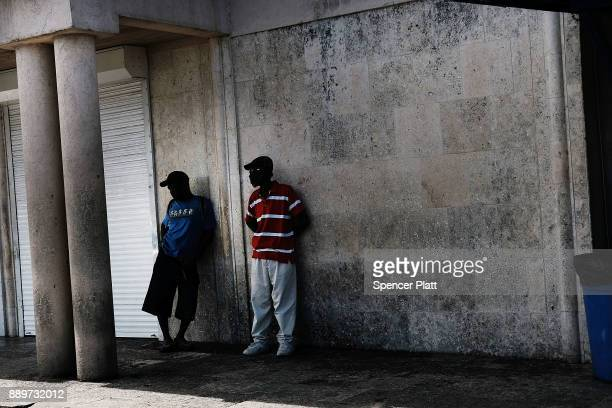 Men pause along a wall on December 10 2017 in St John's Antiqua While it's sister island Barbuda was nearly destroyed by Hurricane Irma Antiqua was...