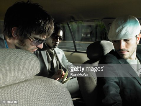 men paying a taxi driver : Stock Photo