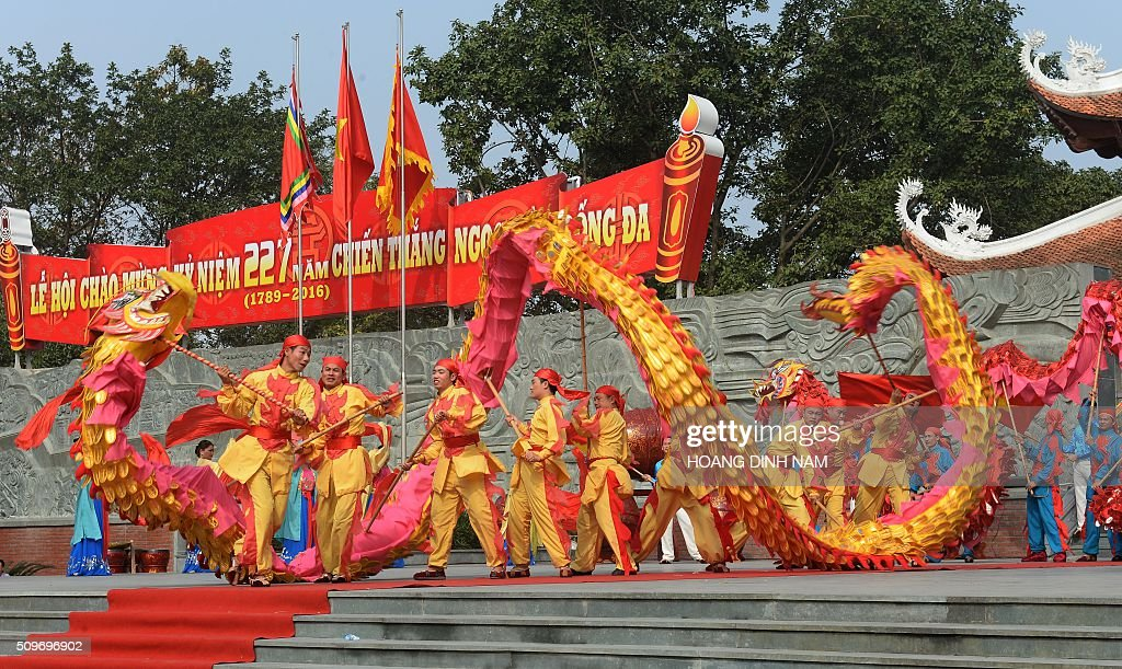 Men perform a dragon dance next to the statue of King Quang Trung during a ceremony marking the 227th anniversary of the Vietnam's Dong Da-Ngoc Hoi victory over China's Qing dynasty's troops in 1789 at a memorial monument to Vietnamese King Quang Trung (1788-1792), winner of the war, in Hanoi on February 12, 2016. AFP PHOTO / HOANG DINH Nam / AFP / HOANG DINH NAM