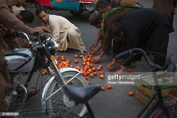 Men pick up fallen tomatoes in the middle of rush hour traffic September 10 2016 in Herat Afghanistan The city lies on the ancient trade routes of...