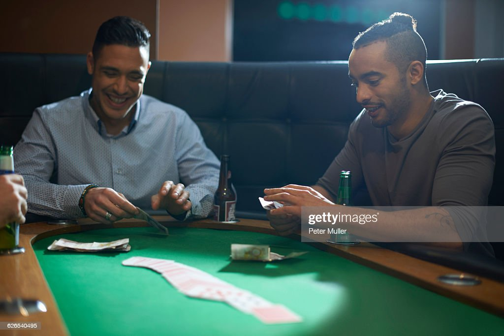 Men placing cash for card game at pub card table