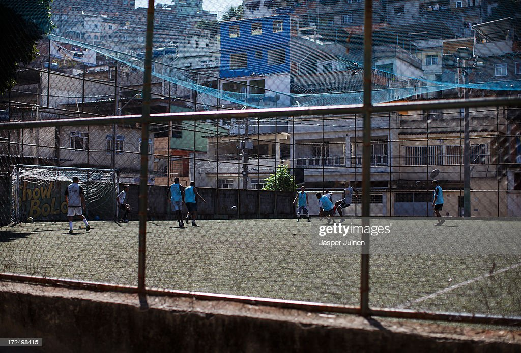 Men play a game of football at the Complexo do Alemao favela on June 29, 2013 in Rio de Janeiro, Brazil. It was at the end of 2010 that under the stage of pacification some 300 police officers went into the Complexo do Alemao with tanks and helicopters to drive out the criminal gangs to establish a permanent police presences and to set up social services such as schools, healthcare centers, and rubbish collection. The Complexo do Alemao favela is, with a population of 100, 000 and stretching for more than 3 kilometers with a maze of narrow alleys and stairways, one of the largest favela's in Rio de Janeiro.