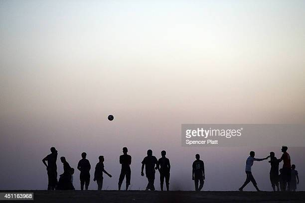 Men play a game of soccer at a temporary displacement camp for Iraqis caughtup in the fighting in and around the city of Mosul on June 24 2014 in...
