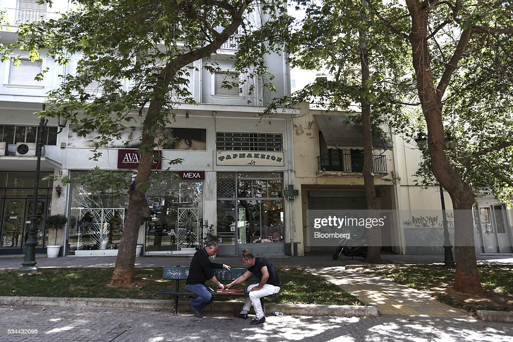 Men play backgammon on a street bench in a square in Athens, Greece, on Thursday, May 26, 2016. Greece may have passed a milestone and its bond market has been lucrative for some investors, but the road to recovery doesn't look much shorter. Photographer: Yorgos Karahalis/Bloomberg via Getty Images