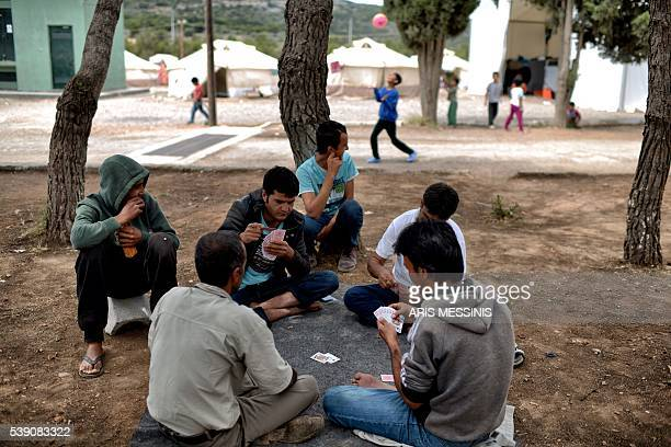 Men play cards as they sit on the ground at the refugee and migrant camp of Schisto in Athens on June 8 2016 Organisers in Greece are taking steps to...