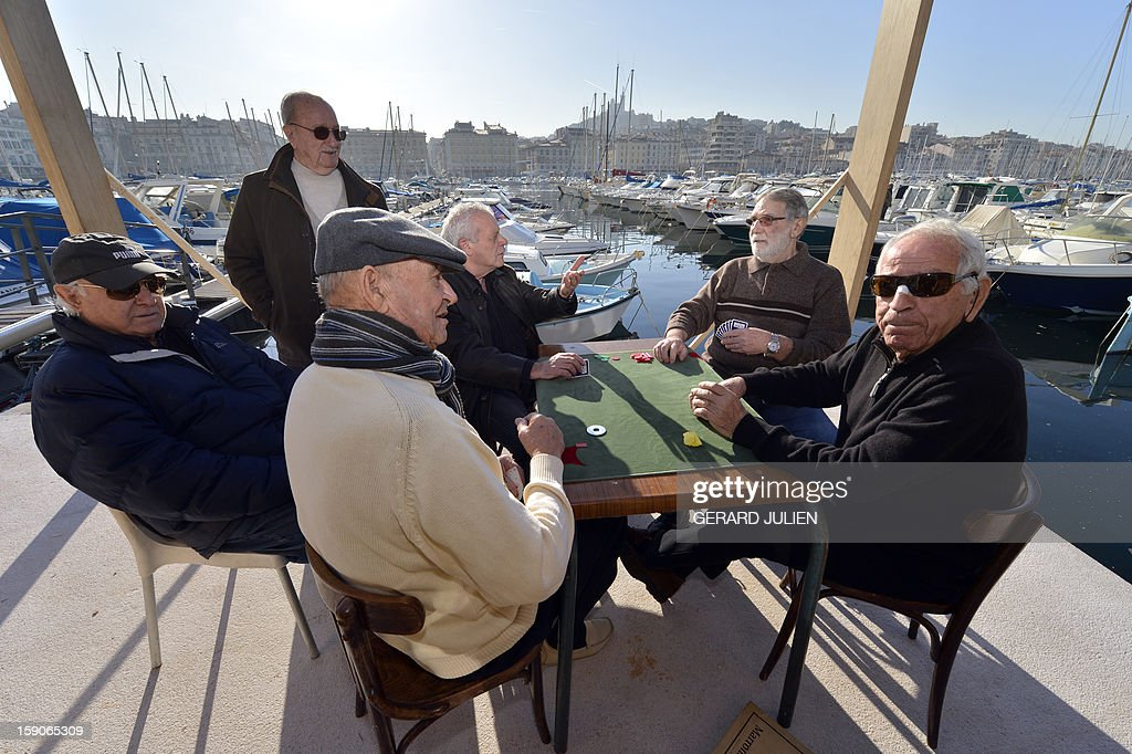 Men play cards on January 7, 2013 in the Vieux Port of Marseille (Marseille's old harbor), southern France, a week before the launching on January 12, 2013 of 'Marseille-Provence European Capital of Culture' in 2013. AFP PHOTO/GERARD JULIEN
