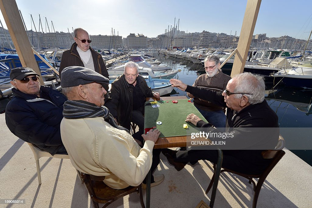 Men play cards on January 7, 2013 in the Vieux Port of Marseille (Marseille's old harbor), southern France, a week before the launching on January 12, 2013 of 'Marseille-Provence European Capital of Culture' in 2013.