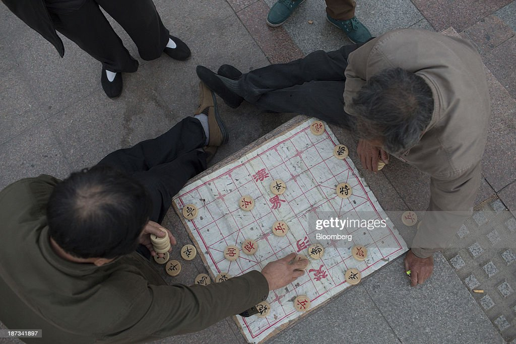 Men play chess at Spring City Square in Jinan, China, on Wednesday, Nov. 6, 2013. The third plenary session of the 18th Communist Party of China Central Committee will be held from Nov. 9 to Nov. 12 in Beijing. Photographer: Brent Lewin/Bloomberg via Getty Images