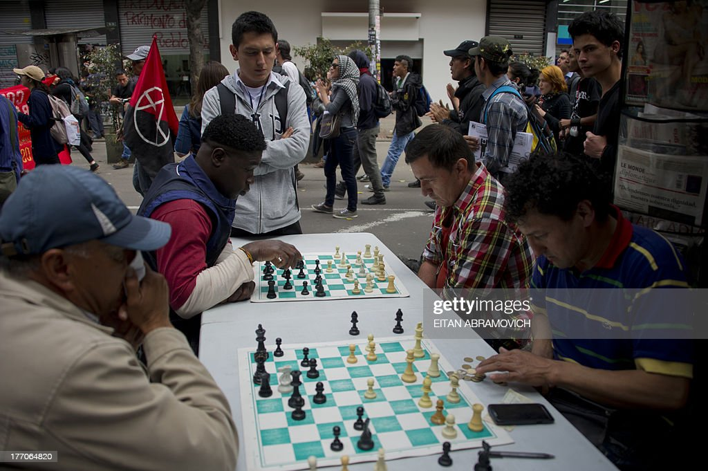 Men play chess next to a rally in support of Colombian farmworkers demanding government subsidies and greater access to land, in Bogota, Colombia, on August 20, 2013. Farmers who want Colombian President Juan Manuel Santos to set up a national dialogue to discuss land and other issues affecting farmworkers, were joined by truckers, miners and health and education workers in nationwide roadblocks, rallies and demonstrations that began on Monday. AFP PHOTO/Eitan Abramovich