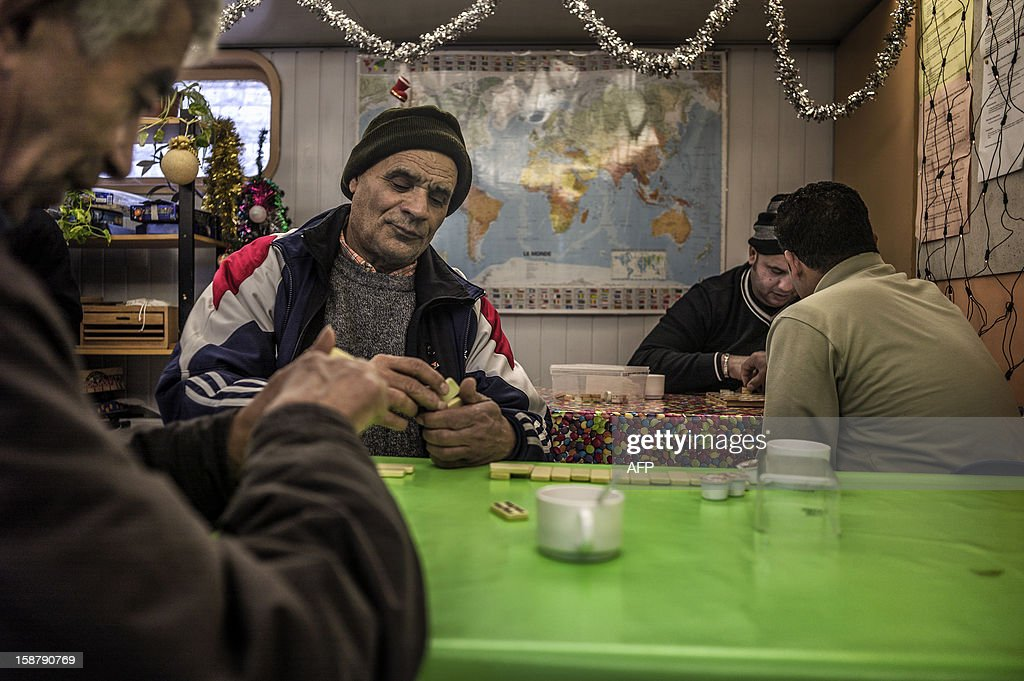 MOUTTET - Men play dominos aboard a barge of charity association 'Peniche Accueil' which welcomes every day in the afternoon homeless and people with financial difficulties, on December 27, 2012 in Lyon.