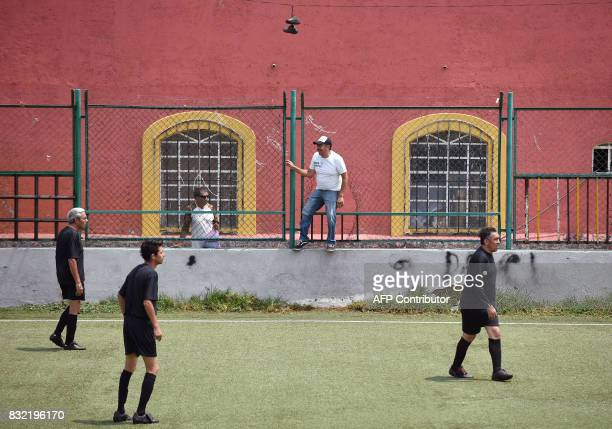 Men play during a match in which both teams have black uniforms as part of a performance called 'Todos Contra Todos' of Chilean artist Camilo Torres...