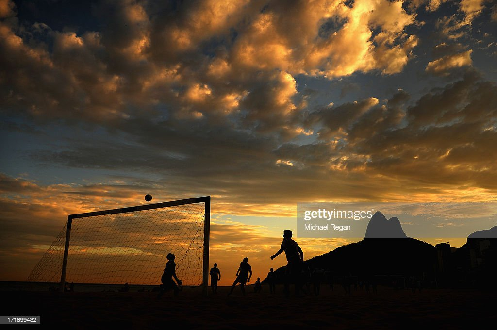 Men play football on Ipanema beach as the sun sets on June 29, 2013 in Rio de Janeiro, Brazil. The final of the FIFA Confederations Cup between Brazil and Spain will take place in the city on June 30.
