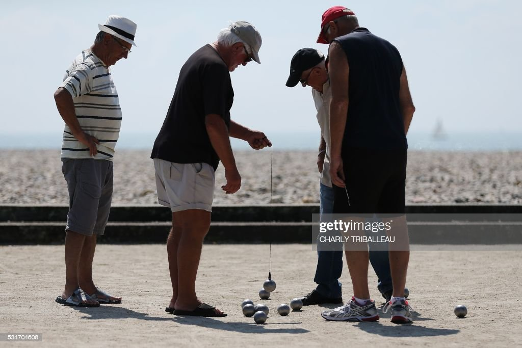 Men play petanque (bowls) next to the sea, in Le Havre, northwestern France, on May 27, 2016. / AFP / CHARLY