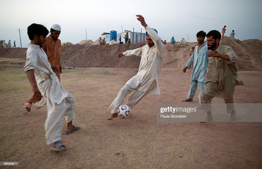 Men play soccer at the massive tent city May 31, 2009 in Jalozai camp, 15 k from Peshawar, Pakistan. According to the NWFP authorities and the UN, at least three million internally displaced persons (IDPs) have now been registered as a result from recent fighting and on-going military operations against the Taliban. The Taliban have fled the Pakistani army's advance on the main town in the Swat Valley, according to the Pakistan military. The refugees have fled from Swat, Buner, and Lower Dir facing extremely harsh living conditions in the searing heat in over crowded camps.