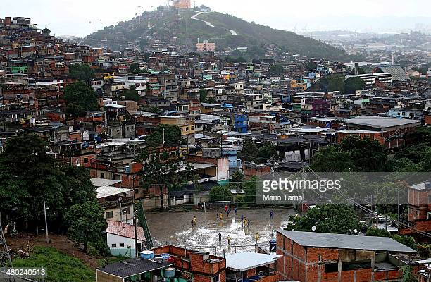 Men play soccer on a muddy field in the Complexo do Alemao pacified 'favela' community on March 23 2014 in Rio de Janeiro Brazil The 'favela' was...