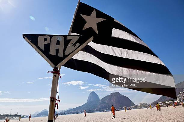 Men play Sunday morning football on Botafogo Beach with Rio de Janeiro's iconic Sugar Loaf Mountain in the background and the flag of Botafogo...