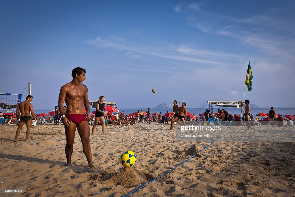 Men play volley-football on beach : Stock Photo