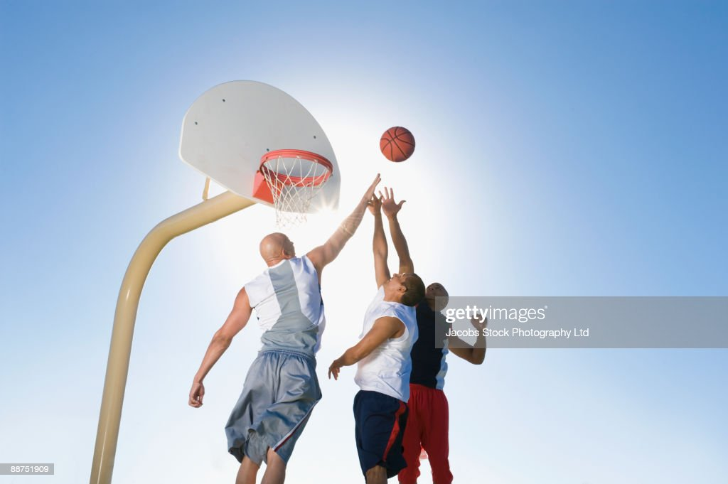 Men playing basketball outdoors : Stock Photo